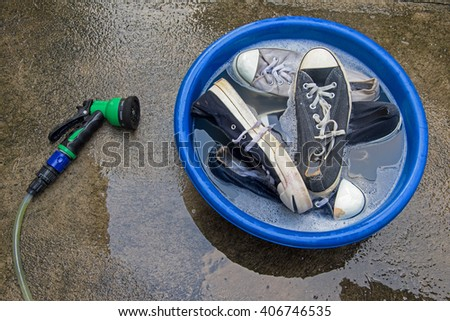 water hose or spray and many Shoes in a wash basin with soapy water - stock photo