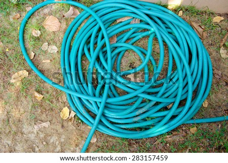 water hoses lie on the garden - stock photo