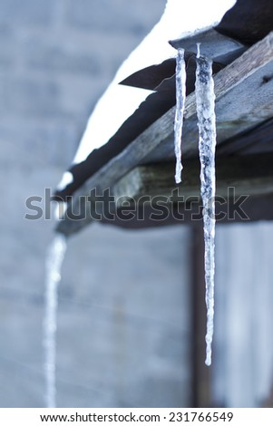 water icicles in winter time from the roof - stock photo