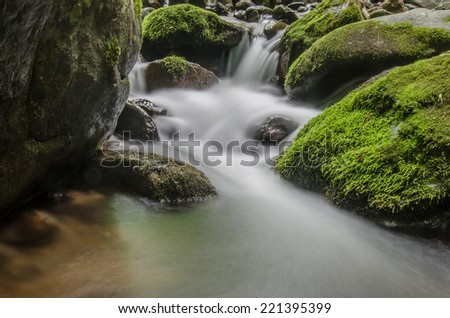 Water in a creek in the mountains of Georgia tumbles over mossy rocks - stock photo