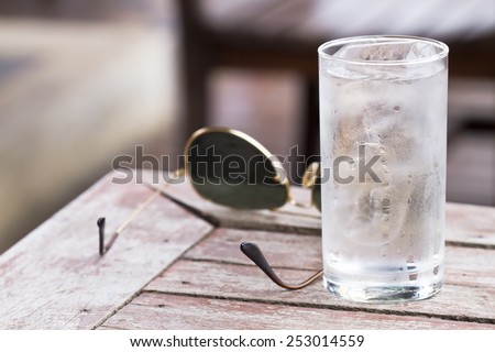 Water in a glass with ice placed on wooden table with glasses for a toast to the health and thirst - stock photo