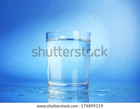 Water in  glass, on dark blue background - stock photo