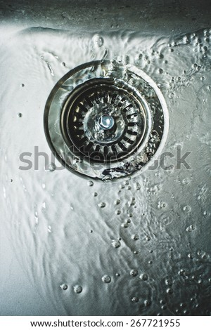 water in the kitchen sink stainless. Reducing water consumption, will help to keep finances - stock photo