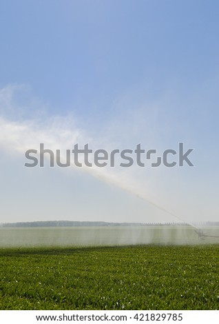 Water irrigation on a green farmland with a great spray of water in a hot summer. - stock photo