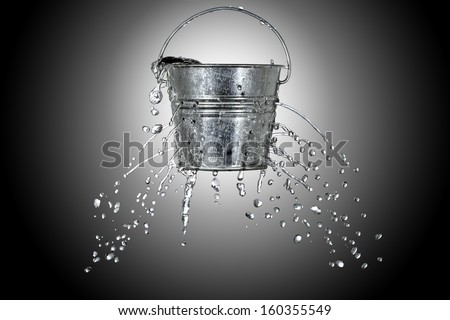 water is coming out of a bucket with holes - stock photo