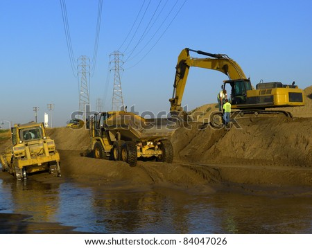 Water is diverted while construction equipment is used to widen and deepen a river bed - stock photo