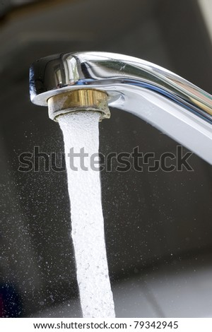 Water is floating from a tap in the kitchen - stock photo