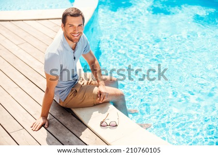 Water is just great! Top view of cheerful young man in polo shirt sitting by the pool and smiling - stock photo