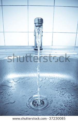 water is running into a washbasin - stock photo