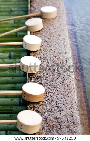 Water Ladles at the purification pavilion, Miyajima Shrine, Miyajima Island, Japan. To clean one's hands is a ritual cleansing (misogi) before entering a Shinto shrine.
