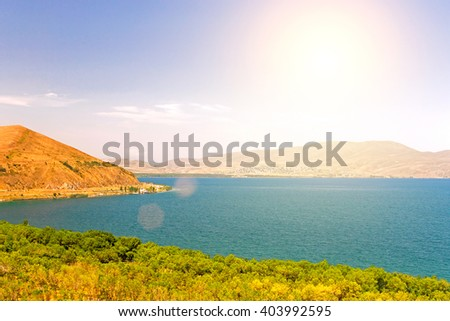 Water landscape: sea, mountain, forest, buildings and blue sky