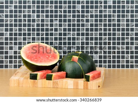 Water Melon halved and cut into fingers on kitchen work top - stock photo