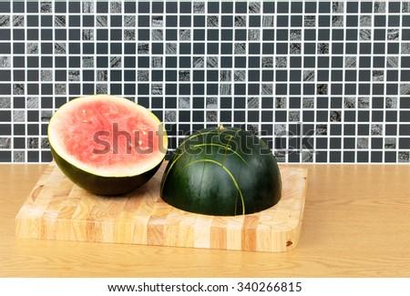 Water Melon halves on kitchen work top - stock photo
