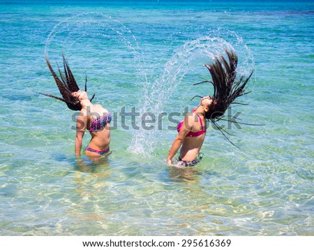 Water motion hair freeze on teenage girls bathing in sea background - stock photo