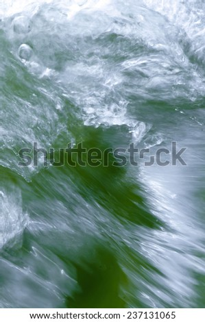 Water of a river in strong motion with white foam - stock photo