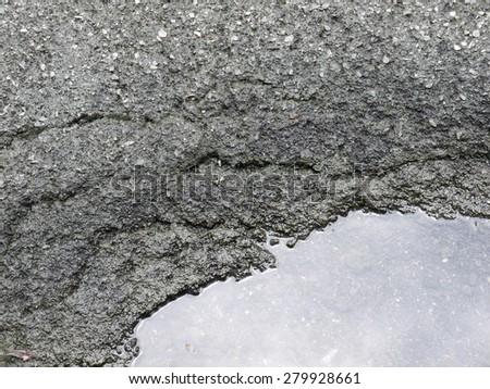 Water on the asphalt road crack - stock photo