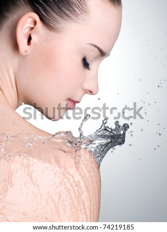 Water on the shoulder of beautiful woman with clean skin - vertical - stock photo