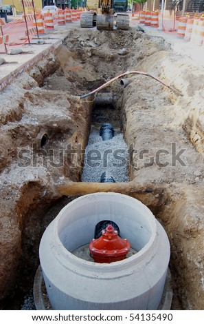Water pipe installation, street construction site with excavator - stock photo