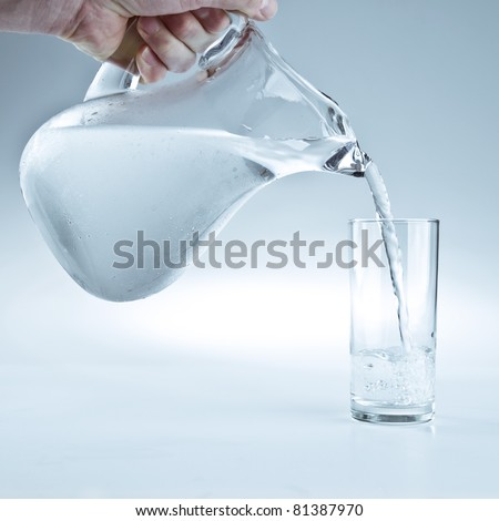 Water pitcher pouring a glass of fresh water - stock photo