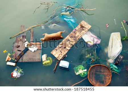 Water pollution with plastic garbage and dirty trash waste. Floating urban debris on contaminated industrial sewage litter stream.   - stock photo