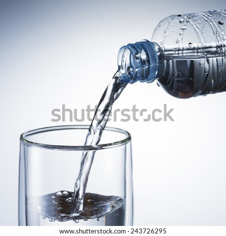 Water Pour from Water Bottle To Glass - stock photo