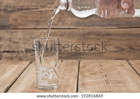 Water pour on to glass on wood table  - stock photo