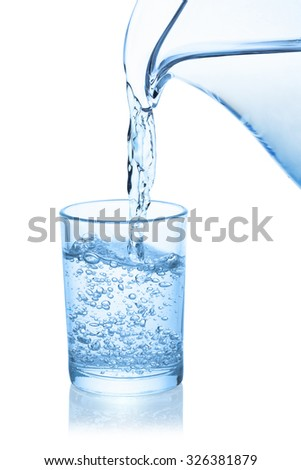 Water poured from the pitcher into a glass, isolated on the white background, clipping path included.