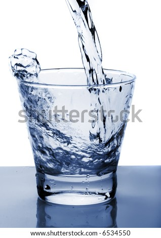 Water poured into glass (toned in blue) - stock photo