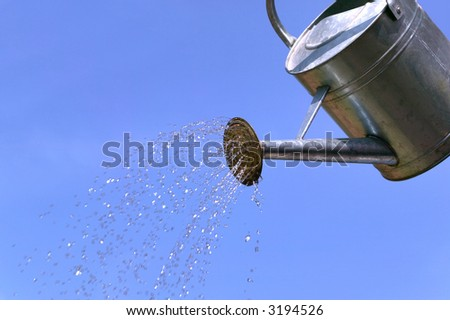 Water pouring from a watering can against a blue sky.