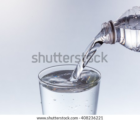 Water pouring from bottle into the glass - stock photo