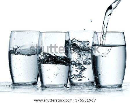 Water pouring in four glasses - stock photo
