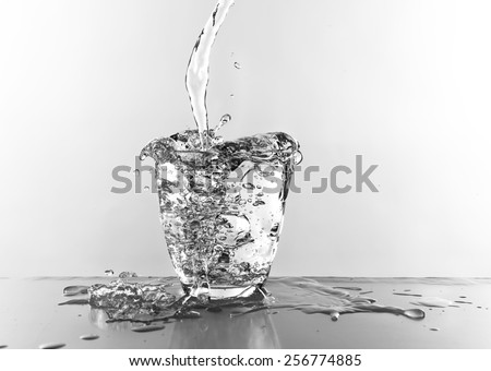 Water pouring in glass isolated on white - stock photo