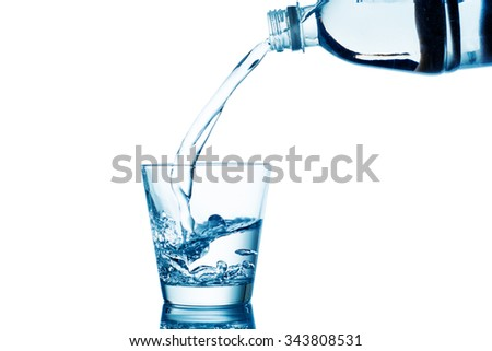 Water pouring in glass with splash isolated on white.