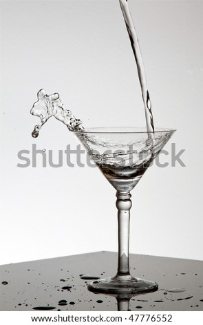Water pouring in Martini glass and spilling out on a shiny surface - stock photo