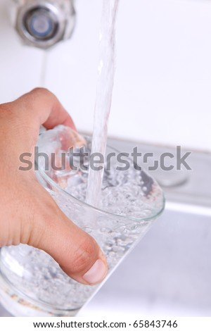 Water pouring into a glass from a faucet - stock photo