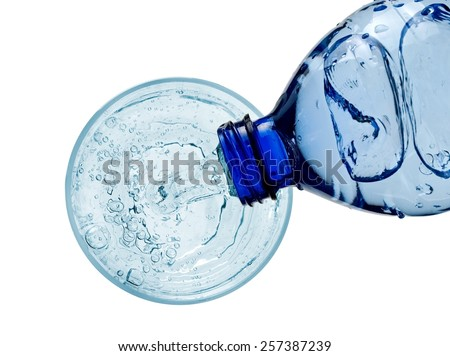 Water pouring into a glass from a plastic bottle, top view - stock photo