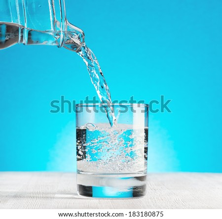 Water pouring into a glass on blue background.