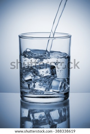 Water pouring into glass with ice cubes - stock photo
