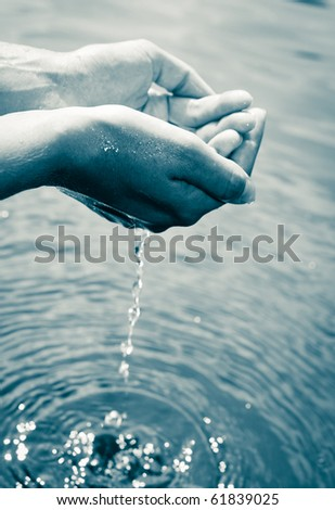 Water pouring out of a young woman's hands - stock photo