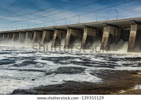 Water pouring through the sleus gates at dam - stock photo