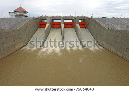 Water pouring through the water gates at dam landscape - stock photo