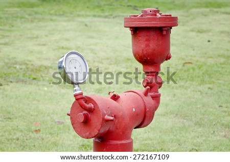 Water pressure meter installed on a red water pipe in the garden - stock photo