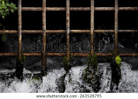 Water privatization concept, water flows from grill spring - stock photo