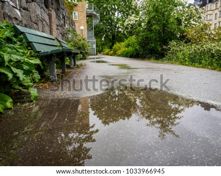 water puddle on the street with green park bench on the side