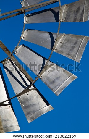 Water pump windmill  metal vanes against clear blue sky - stock photo