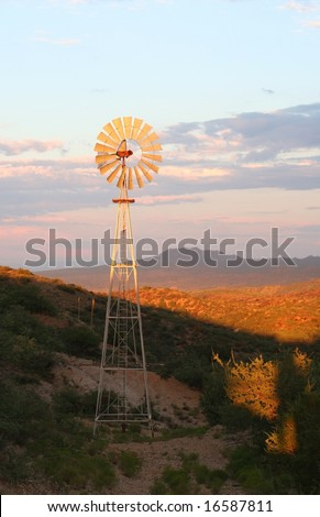 Water pumping windmill lit up at sunset in the Arizona desert.