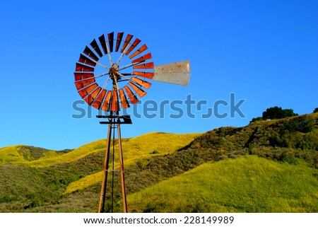 Water pumping windmill with a hill and blue sky in the background. - stock photo