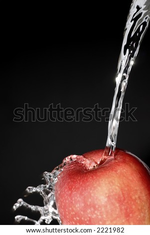 water puring on an apple in front of black background - stock photo