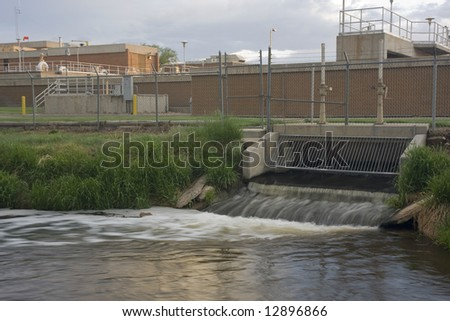 Water reclamation plant with processed and cleaned sewage flowing out to the river - stock photo