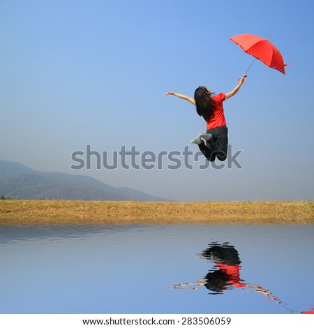Water Reflection Red umbrella woman and blue sky.Copy space - stock photo